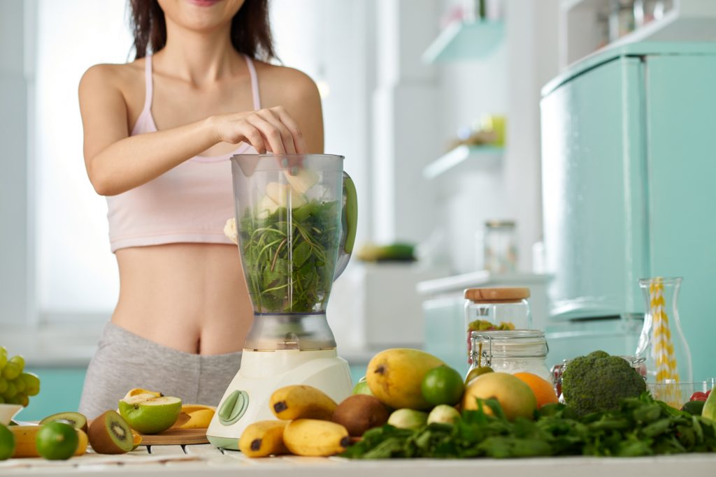 Woman preparing fruit and greens smoothie in blender